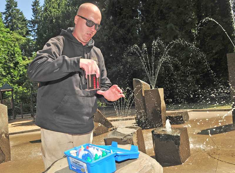 TIDINGS PHOTO: VERN UYETAKE  - Park maintenance worker Will Yates checks the ph level at the Robinwood Park splash pad.