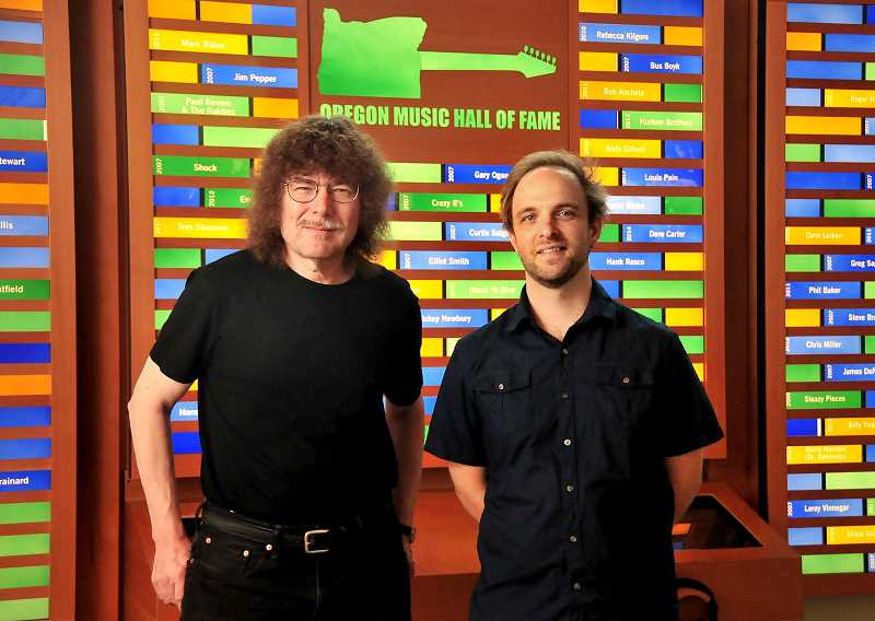 TIDINGS PHOTOS: VERN UYETAKE - Oregon Music Hall of Fame co-founder Terry Currier, left, and Youth Music Project Executive Director Travis Magrane pose in front of the Hall of Fame display at Youth Music Project in West Linn.