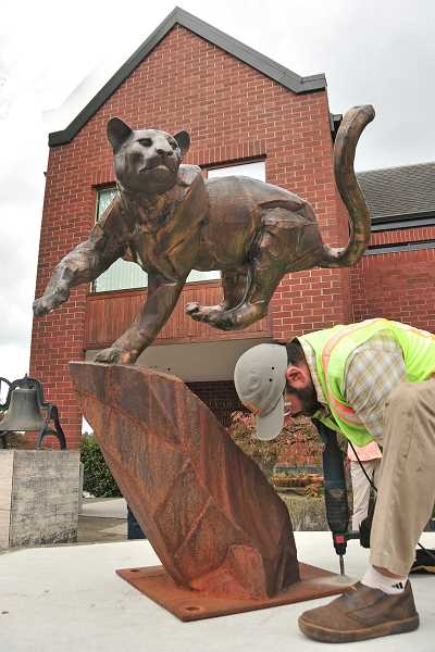 REVIEW PHOTO: VERN UYETAKE - Arts Council volunteer Mike Suri drills holes Friday during the installation of 'Cougar on the Run.'