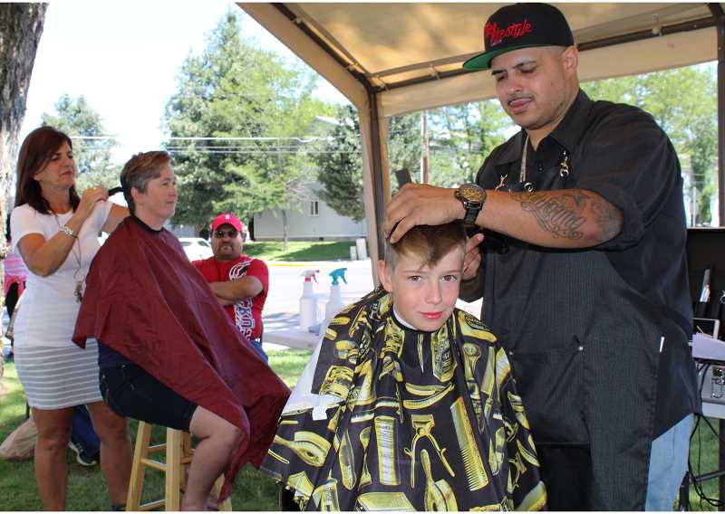 HOLLY M. GILL - From left to right, Kim Glaspie cuts Malissa Hilton's hair, while 13-year-old Tylir Anderson gets his hair cut by Pedro Hernandez.