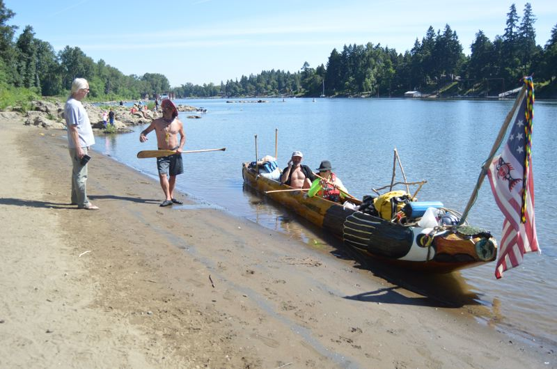 SPOTLIGHT PHOTO: NICOLE THILL-PACHECO - Willow Bill Goulardt, center left, talks with a man on the banks of the Willamette River while taking a short break during a paddle trip with the Flying Eagle canoe earlier this summer. In the canoe, Steve Beckmann, a Seattle resident, and Patrick Birkle, a St. Helens resident, take a short break to reapply sunscreen before heading back out on the water to head to Willamette Falls.