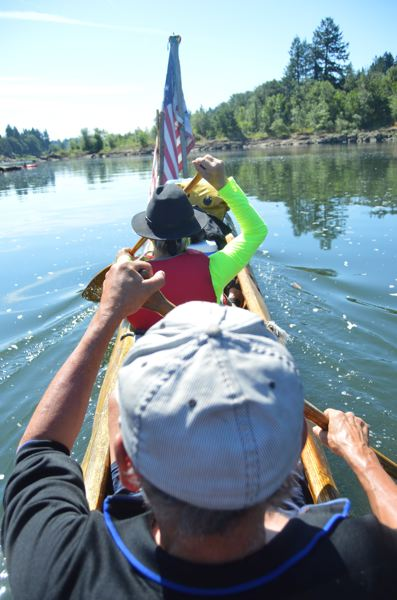 SPOTLIGHT PHOTO: NICOLE THILL-PACHECO - Patrick Birkle, a St. Helens resident, and Steve Beckmann, a Seattle resident, pictured here, paddle the Flying Eagle canoe down the Willamette River on a June 2018 afternoon. Not pictured, Willow Bill Goulardt, helps steer the canoe from the rear position and watches for river currents to make easier movements in the water.
