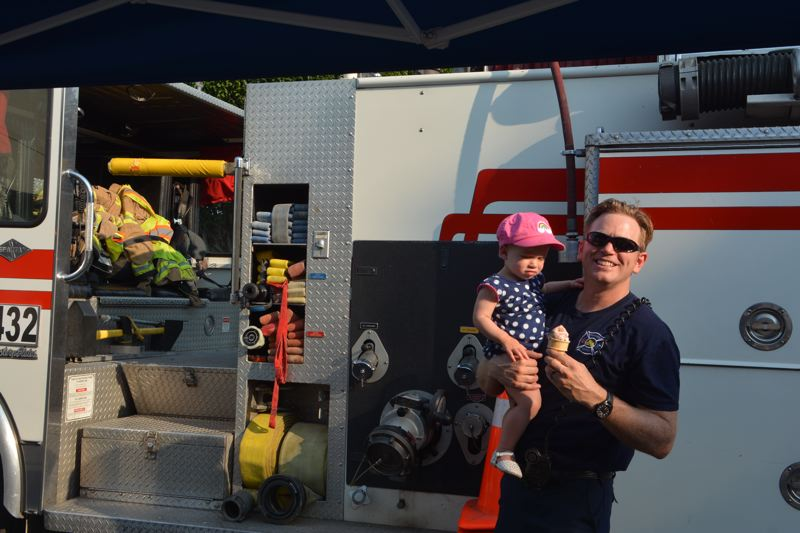 SPOTLIGHT PHOTO: COURTNEY VAUGHN - Zach Ahlers, a Scappoose firefighter, holds his daughter, 1 -year-old Zoey, while enjoying an ice cream cone, courtesy of the Watts House Pioneer Museum in Scappoose. Police and firefighters were part of the National Night Out community event at Heritage Park in Scappoose.