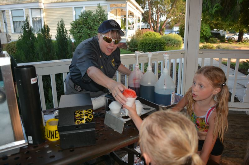 SPOTLIGHT PHOTO: COURTNEY VAUGHN - Scappoose Police Department Chaplain Patricia Altimus serves shaved ice to children during National Night Out in Scappoose Tuesday evening.