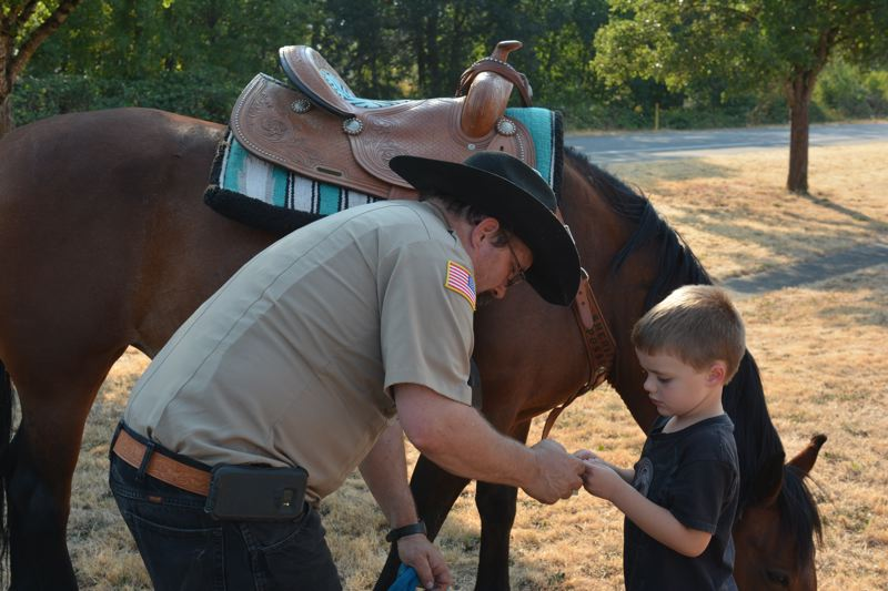 SPOTLIGHT PHOTO: COURTNEY VAUGHN - David Somann with the Columbia County Sheriff's Office Mounted Posse, gives 4-year-old Owen a sticker to keep during a National Night Out event Tuesday, Aug. 7.