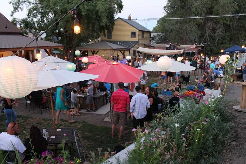 HOLLY M. GILL/MADRAS PIONEER - A large crowd enjoys Precious Byrd, of Bend, sponsored by Madras Sanitary Service, at Wild Bleu, one of many businesses participating in the First Thursday Park and Play in downtown Madras on Aug. 2.