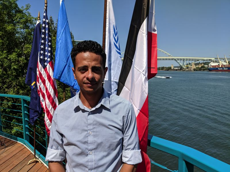 "PAMPLIN MEDIA GROUP: JOSEPH GALLIVAN - Local Yemeni-American Khalid Almaktari, standing in front of an upside-down Yemeni flag, works for UTI in inventory management with Intel. ""Oregon became my home in 2011, but I have a lot of family in Yemen."""