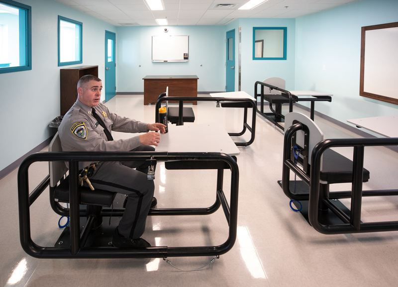 JON HOUSE/PORTLAND TRIBUNE - Corrections Capt. Toby Tooley sits in an inmate chair inside one of the classrooms at the new behavioral health treatment center at Oregon State Penitentiary in Salem.