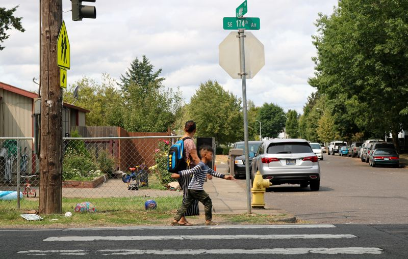 TRIBUNE PHOTO: ZANE SPARLING - Two people walk along Southeast 174th Avenue on Sunday, August 12.