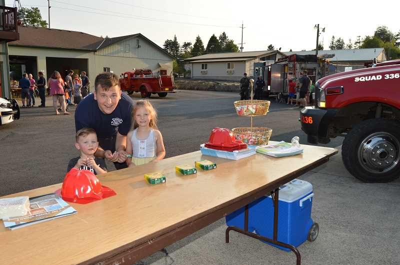 PIONEER PHOTO: CINDY FAMA - Hendrix, 2, and Cooper, 5, visit the fun table with volunteer firefighter Elijah Liles.