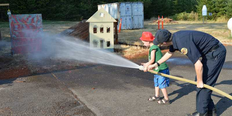 PIONEER PHOTO: CINDY FAMA - Tanner Priest, 5, puts out fires with the help of Colton volunteer firefighter Aaron Myers.