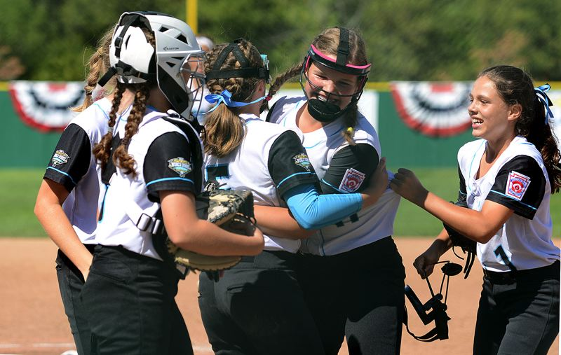 PAMPLIN MEDIA GROUP: MILES VANCE - Shelby Moore of Lake Oswego (Oregon District 4) is mobbed by teammates after making a lunging catch for the final out to secure Saturday's 3-2 win over Wheelersburg, Ohio, in the Little League Softball World Series at Alpenrose Stadium.