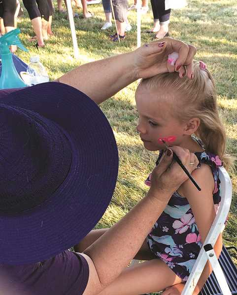 PIONEER PHOTO: CAROL ROSEN - Five-year old Alice Hepler gets her face painted by City Council Member Delise Palumbo.