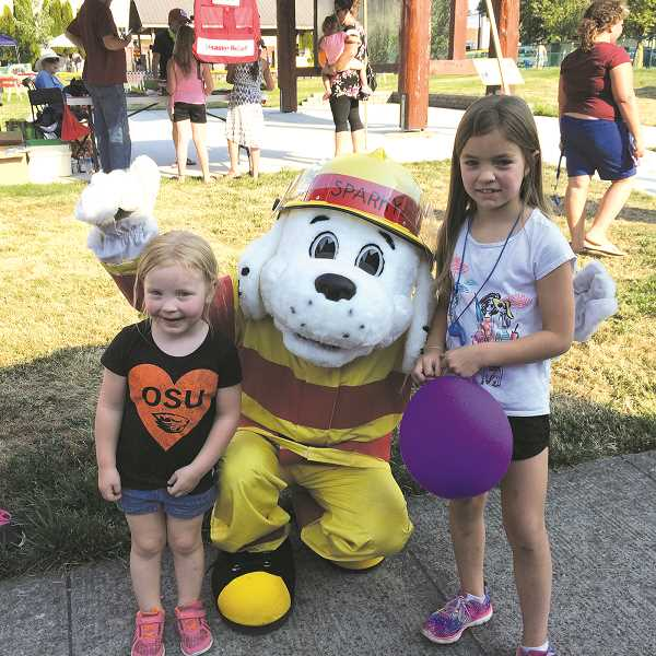 PIONEER PHOTO: CAROL ROSEN - Sparky, the fire dog hugs Daphne (age 4) and Mckayla (age 7) Duncan.