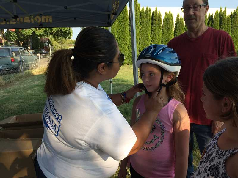PIONEER PHOTO: CAROL ROSEN - Christina Reynaga fits Savanna Cole, age 9, with a free bike helmet. Reynaga works for Molalla Communications in customer service. Every year at National Night Out, Molalla Communications fits free bike helmets for kids.