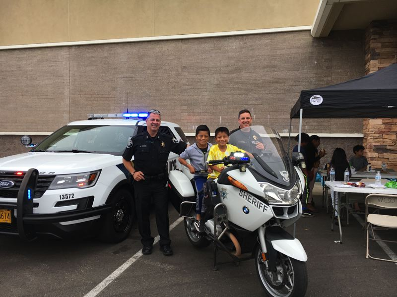 COURTESY PHOTO: WASHINGTON COUNTY SHERIFF'S OFFICE - Cornelius Police Chief Al Roque and a deputy pose with children at Saturday's Backpacks and Snacks event outside Walmart.