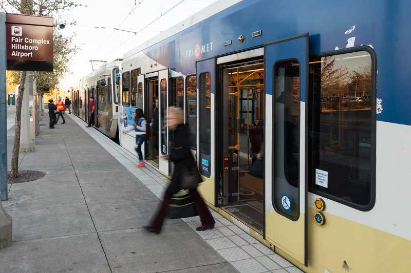 STAFF PHOTO: CHRISTOPHER OERTELL - Passengers disembark from MAX light rail at the Fair Complex stop in Hillsboro. Crews will be replacing white safety tiles at the station for the next month.