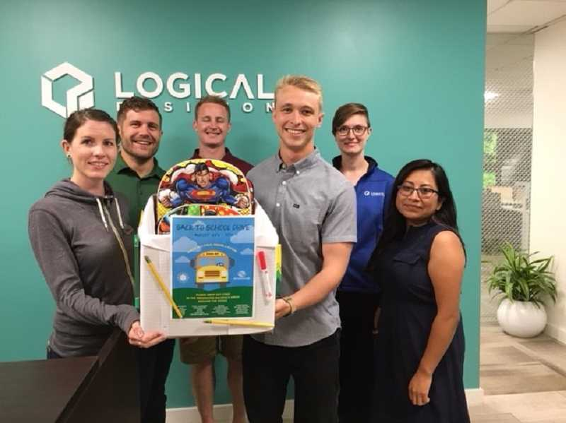 SUBMITTED PHOTO - Gathering around a donation box for the Boys & Girls Club of America are Logical Position employees. They are asking the public to donate school supplies for the benefit. All seven LP offices in the United States are collecting school supplies for local chapters of the Boys & Girls Club of America.