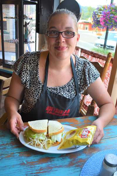 ESTACADA NEWS PHOTO: EMILY LINDSTRAND - Erin Brittle shows off the Mason Jars cucumber sandwich. Sandwiches at The Mason Jar are served with chips and a pickle.