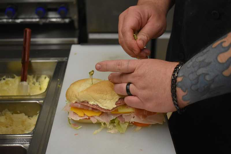 ESTACADA NEWS PHOTO: EMILY LINDSTRAND - Matty Flink puts the finishing touches on the Matty Bomb sandwich.
