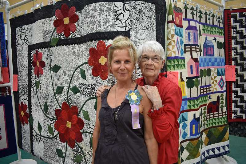 ESTACADA NEWS PHOTO: EMILY LINDSTRAND - Vickki Cox and her aunt, Garfield Skip-a-Week Club show featured artist Judith Bay, smile in front of a small selection of quilts included in the show last week.