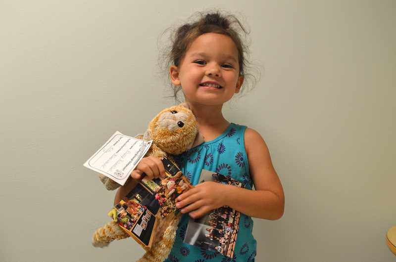 SUBMITTED PHOTO: SARAH FLATHMAN  - Poppy Richardson picks up her stuffed cat from the animal sleepover the next day.