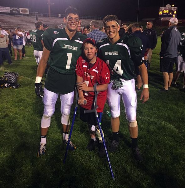 CONTRIBUTED PHOTO - Wyatt Riedel (right) stands with Ted Wickman from Yoncalla and a child from the Shriner's hospital after the all-star game earlier this month in Baker City.
