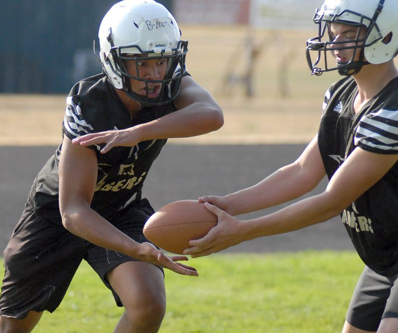 ESTACADA NEWS: MATT RAWLINGS - Estacada running back Gabe Martinez takes a handoff during the first day of football practice Monday morning. The Rangers compete in the Seaside jamboree on Friday, Aug. 24, before hosting Valley Catholic in their season opener on Friday, Aug. 31.