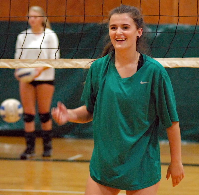 ESTACADA NEWS: MATT RAWLINGS - Sidnee Keller shares a smile at the net during the opening session of practice with the volleyball team, which is welcoming new coach Mike King to the sideline. The Rangers open the season at home Thursday, Aug. 30, against Astoria.
