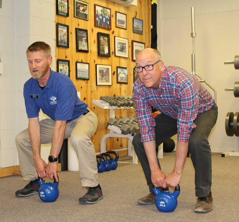 HOLLY GILL/MADRAS PIONEER - Apex owner Brock Monger, left, shows the congresssman correct form for lifting a weight.