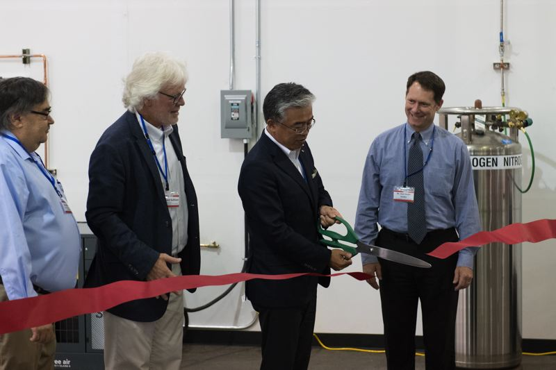 STAFF PHOTO: CHRISTOPHER OERTELL - Yamaki Co. President Yoshihiro Kido cuts the ribbon at Yamaki USA, as (from left) Jeff King, Forest Grove's economic development manager; Howard Sullivan, executive director of the Forest Grove/Cornelius Chamber of Commerce; and Jesse VanderZanden, Forest Grove's city manager, look on.