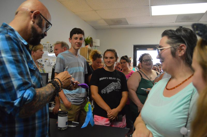 SPOTLIGHT PHOTO: NICOLE THILL-PACHECO - Jackson Galaxy, left, autographs a cat toy for Mandy and Ava Manke, far right, during his visit on Aug. 9. Galaxy posed for photos with fans and signed autographs on phone cases, cat toys and books during his visit.