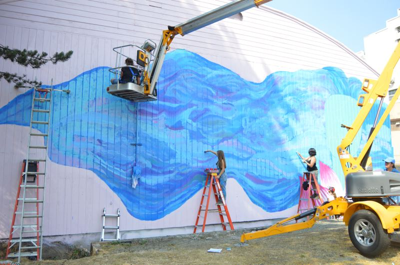 SPOTLIGHT PHOTO: NICOLE THILL-PACHECO - A group of Columbia County students work on different elements of a 25-by-50-foot mural the designed on Friday, Aug. 10. The finished mural depicts a female face emerging from a flower with long blue hair filled with sea creatures.