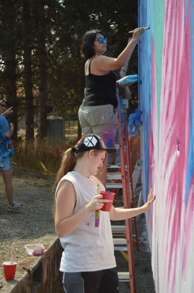 SPOTLIGHT PHOTO: NICOLE THILL-PACHECO - In the foregroun Klair Nelson uses her hand to fill in shaded areas of a bright pink flower on the mural, while Kenda Ericson, background, uses a brush to touch up the hair of the woman in the mural.