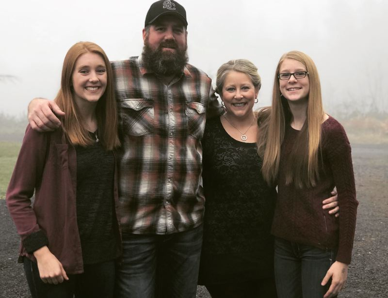 SUBMITTED PHOTO - St. Helens basketball standout Maddie Holm (left) will return to lead the Lion girls basketball team in the 2018-19 season, supported as always by her family, father Nate, mother Melissa and sister Katie.