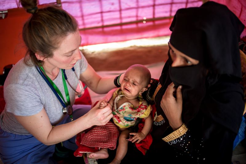 PHOTO COURTESY OF JENNY STOECKER - A Medical Teams International health worker tends to a baby in a refugee camp in Bangladesh.