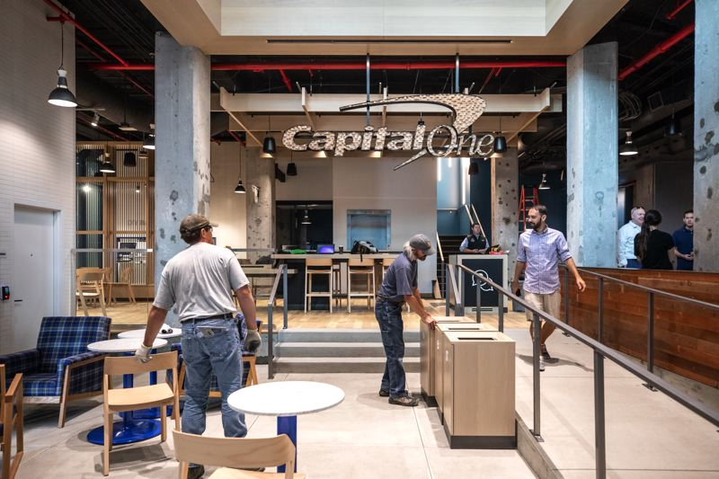 TRIBUNE PHOTO: JONATHAN HOUSE - Construction workers put the finishing touches to the Capital One Café, which is designed to feel more like a coffee shop than a bank. Ambassadors will greet people to see if they have come for a banking issue of just a cup of Peet's.