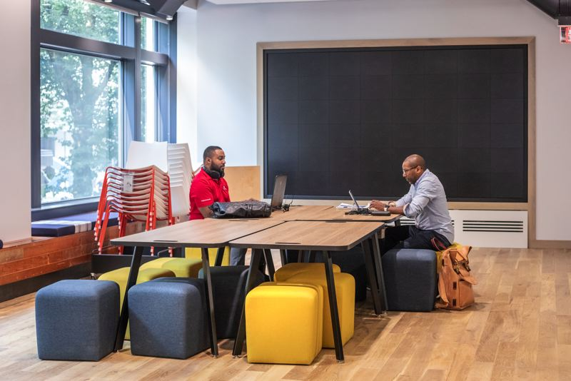TRIBUNE PHOTO: JONATHAN HOUSE - Jerrell Harris, left, and Greg Alston work in the community space at the new Capital One Cafe.