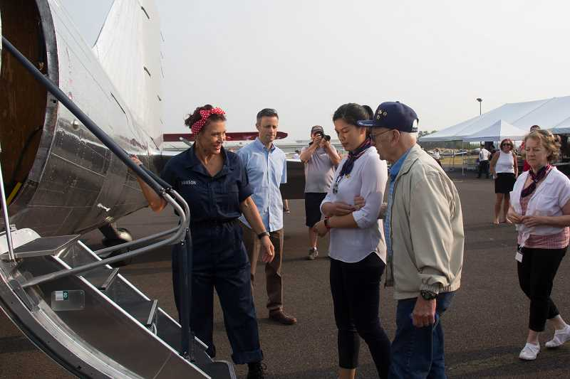 COURTESY PHOTO: THE VITAL LIFE FOUNDATION - 'Rosie the Riveter' helps veterans aboard the DC3 plane during the Spirit of '45 event at Aurora State Airport.