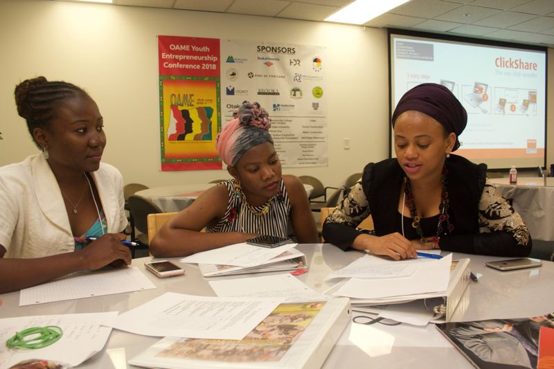 PAMPLIN MEDIA GROUP: STEPHANIE BASALYGA - Abiba Magba, left, and Isatou Barry, right, discuss their business plan with a third team member during the recent Youth Entrepreneurship Conference hosted by OAME.  Both Magba and Barry are on track to earn college degrees in business-related fields.