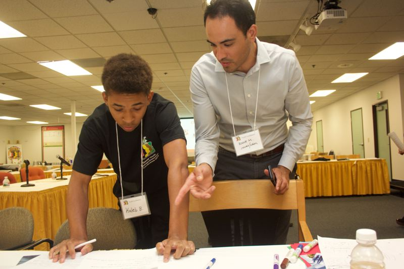 PAMPLIN MEDIA GROUP: STEPHANIE BASALYGA - Business professionals like Jacobs Engineering's Eddie Montejo, right, helped conference participants develop their business plans.