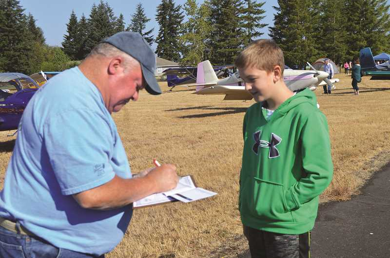 PIONEER PHOTO: CINDY FAMA - Wyatt Holliday receives his first entry into his flight log book from local pilot Bob Lewis.