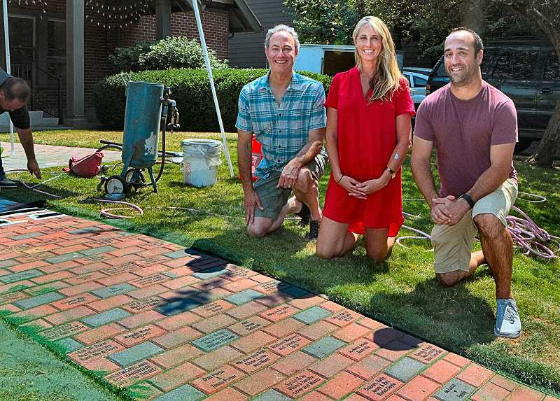 DAVID F. ASHTON - SMILE Board President Joel Lieb, with Board members Kim Borcherding and Kevin Palmer, examined the newly engraved bricks in the SMILE Brick Pathway - while the engraving was still underway, at far left.