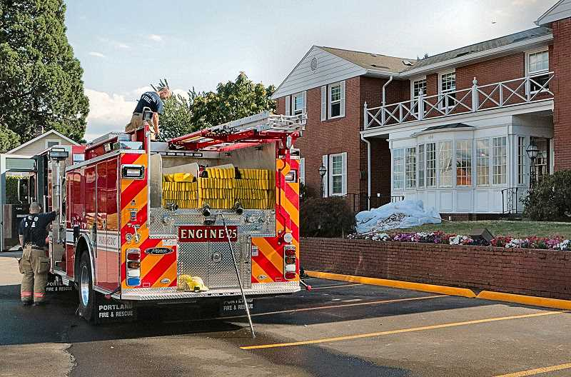 DAVID F. ASHTON - After extinguishing an attic fire in this Creston-Kenilworth neighborhood funeral home, the crew of PF&R Station 25s Engine Company stows their gear.
