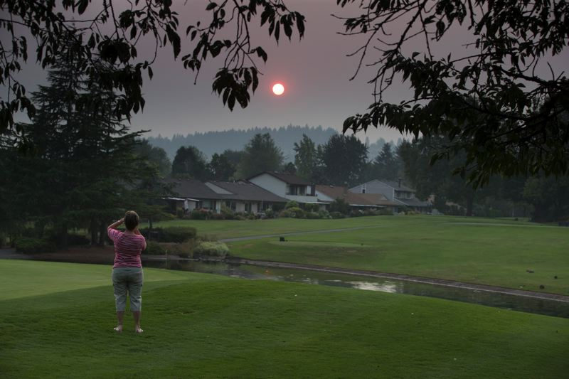 TIMES PHOTO: JAIME VALDEZ - Summerfield resident Janis Pfannenstiel takes a photo from her cell phone of the red sunset at the Summerfield Golf Course.