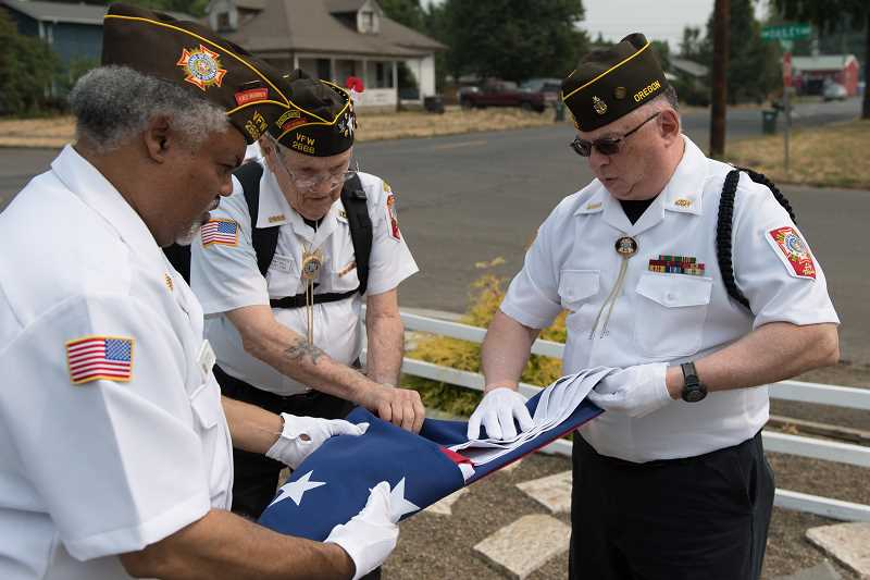 STAFF PHOTO: CHRISTOPHER OERTELL - Andrew Eason, Ellsworth Bell and Mike Hyde fold a 13-star American flag at Hillsboros VFW Post 2666 on Aug. 20. Next week, members of the VFW will perform military honors on a Revolutionary War soldier who died in the Battle of Long Island. His descendents settled in the Hillsboro area.