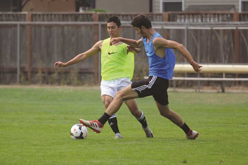 PHIL HAWKINS - Senior Edwin Silva (left) fights for possession with junior Riley Menezes at tryouts last week. The pair is part of a strong core of returning starters that will feature heavily in Woodburn's attempt to win its sixth state title since 2010.