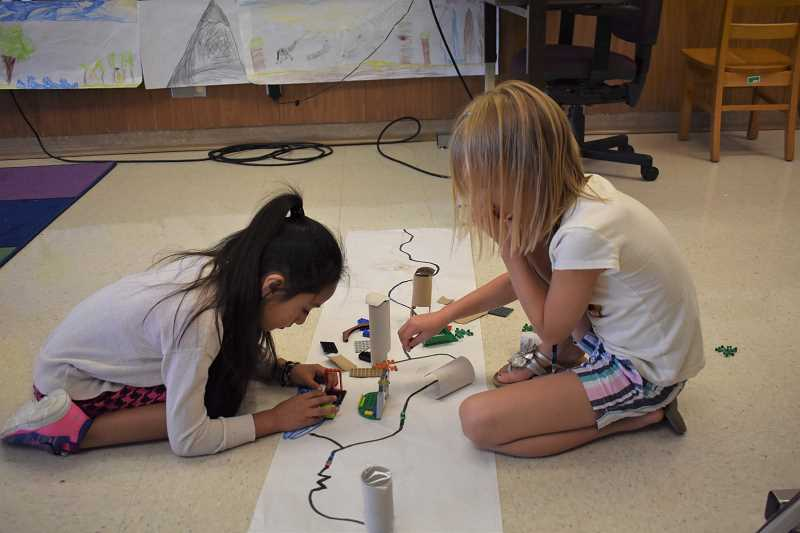 ESTACADA NEWS PHOTO: EMILY LINDSTRAND - Students in a STEM class create cities for their Ozobot robots to move through.