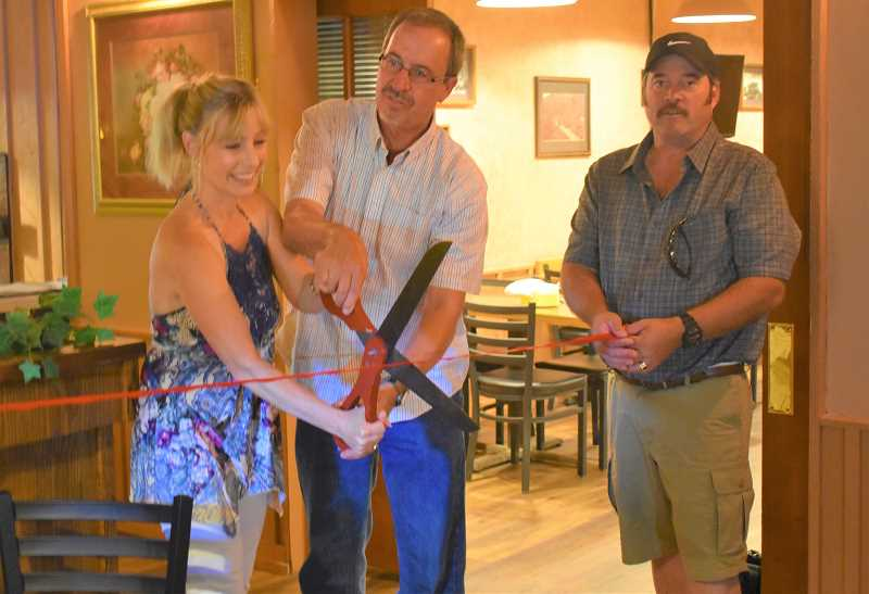 ESTACADA NEWS PHOTO: EMILY LINDSTRAND - Sherry Andrus of The Cazadero, Chamber of Commerce President Brent Dodrill and Mayor Sean Drinkwine prepare to cut the ribbon during the restauraunt's grand opening celebration.