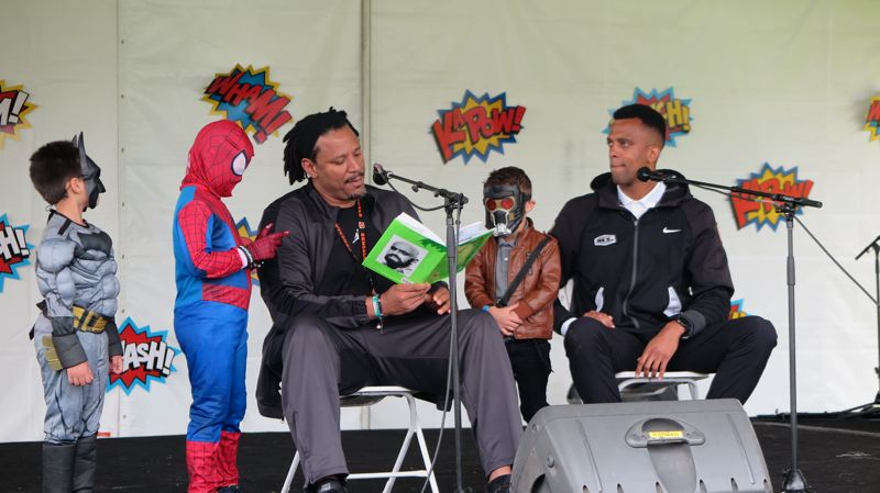 COURTESY PHOTO: LISA OBUNGE - Former NBA player Brian Grant, left, and David Lucas, executive director of the Maurice Lucas Foundation, read to kids during the 2017 Rock the Block.